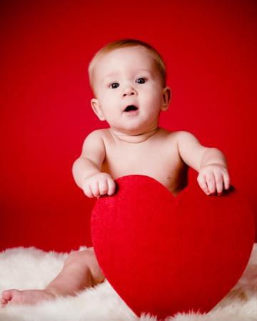 زمینه قرمز و یک بالش قلبی قرمز در دست نوزاد