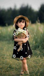 دختر بچه همراه دست گل در فضای باز آتلیه کودک تهران