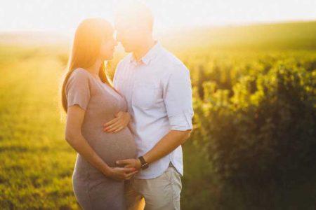 خانم باردار همراه همسر در فضای باز در آتلیه بارداری